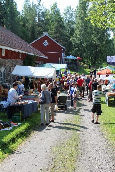 Satoja ihmisiä vierailee kartanon pihapiirissä heinäkuisena päivänä, kun alueella järjestetään koko kylän Kesäpäivä.